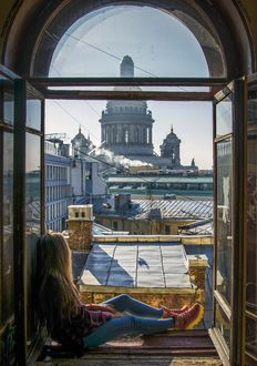 Фото Девушка сидит на подоконнике, любуясь Санкт-Петербургом
