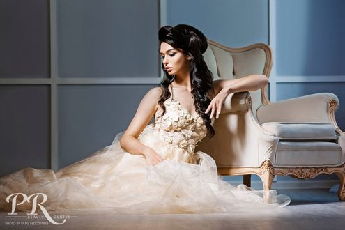 Фото Красивая темноволосая девушка в кремовом платье сидит на полу у кресла и смотрит вниз. Фотограф Олег Федосенко