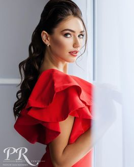 Фото Красивая темноволосая девушка в красном стоит у окна. Фотограф Олег Федосенко