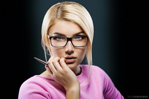 Фото Модель Вика со светлыми волосами в очках держит ручку в руке на темном фоне. Фотограф Олег Федосенко