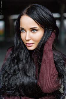 Фото Темноволосая модель Ангелина смотрит в сторону поправляя рукой волосы на размытом фоне. Фотограф Олег Федосенко