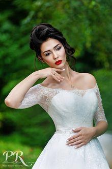 Фото Модель Юлия с каштановыми волосами, в белом платье касается рукой лица и смотрит в сторону на размытом фоне природы. Фотограф Олег Федосенко