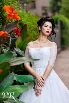 Фото Модель Юлия с каштановыми волосами, в белом платье стоит у веток с цветами на размытом фоне природы. Фотограф Олег Федосенко