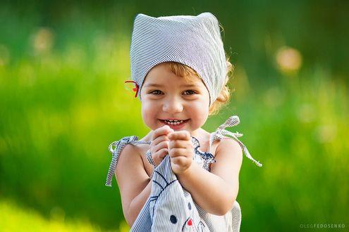 Фото Смеющаяся маленькая девочка в полосатой косынке и сарафане на размытом фоне природы. Фотограф Олег Федосенко