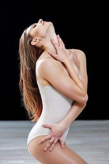 Фото Модель Екатерина в светлом купальнике с закрытыми глазами, подняла голову вверх, касаясь руками своего тела и лица. Фотограф Олег Федосенко