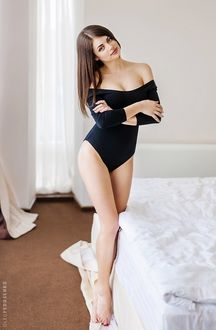 Фото Модель Лена в темном купальнике, сложив руки на груди стоит у постели. Фотограф Олег Федосенко