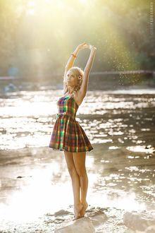 Фото Модель Дарья со светлыми волосами, в разноцветном платье в клеточку, подняв руки над головой, стоит на носочках у воды. Фотограф Олег Федосенко