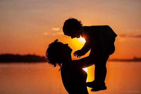 Фото Девушка подняла на руках над собой смеющегося ребенка на фоне закатного неба, Фотограф Олег Федосенко