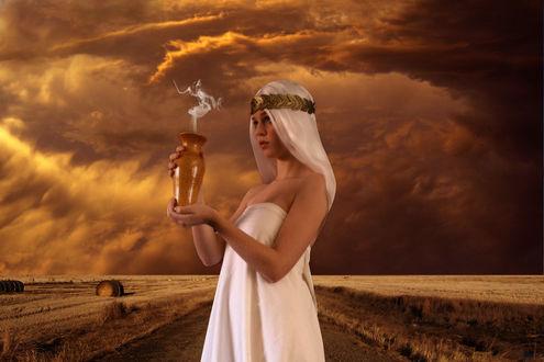 Фото Светловолосая девушка в белом, с украшением на голове держит в руке вазу, из которой идет дым на фоне природы, by amiens