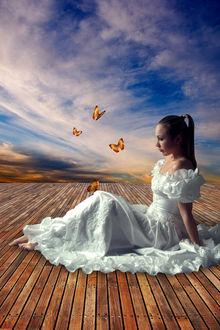 Фото Девушка в длинном белом платье сидит на деревянной поверхности, рядом с ней летают бабочки на фоне неба с облаками, by amiens