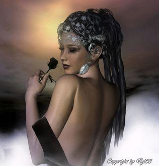 Фото Красивая девушка с черной розой в руке, украшениями на голове, в ушах, стоит на фоне вечернего неба, тумана, автор Elke Krueger