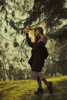Фото Девушка с рыжими волосами стоит на фоне природы и держит рукой волосы, фотограф Marta Bevacqua