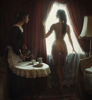 Фото Обнаженная девушка в прозрачной одежде стоит у окна спиной к нам, рядом стоит у стола служанка и наливает чай в кружку. Фотограф Давид Д