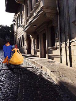 Фото Красавица и чудовище под руку идут по улицам города Баку