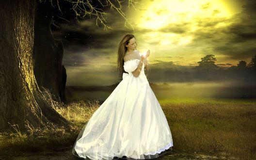 Фото Девушка в белом длинном платьес магией в руках на фоне природы