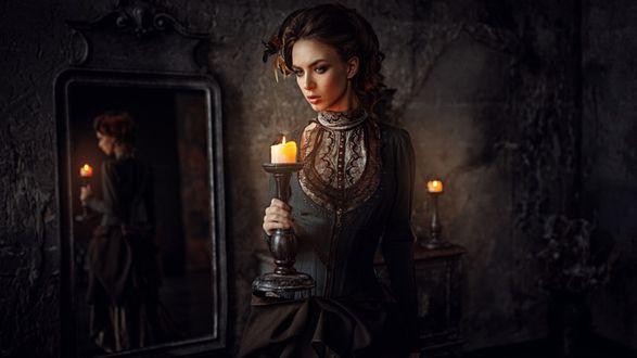 Фото Девушка с подсвечником в руке стоит у зеркала, отражаясь в нем, фотограф Георгий Чернядьев