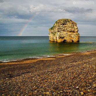Фото Одинокая скала в воде на фоне морского пейзажа с радугой, by Adrian Petrisor