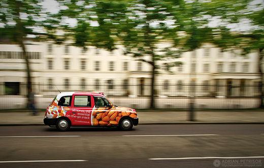 Фото Автомобиль с рекламой орехов мчится по дороге Лондонской улицы на размытом фоне, by Adrian Petrisor