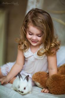 Фото Светловолосая девочка с кудряшками, улыбаясь смотрит на кролика, фотограф Виктория Старцева