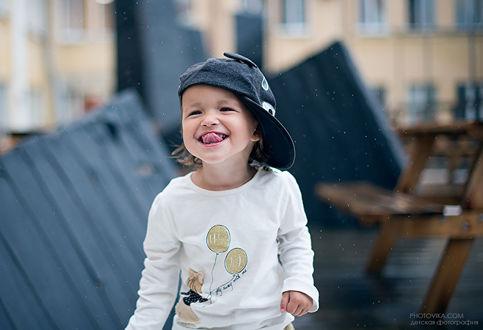 Фото Улыбающийся мальчик с высунутым языком в кепке на крыше дома, фотограф Виктория Старцева
