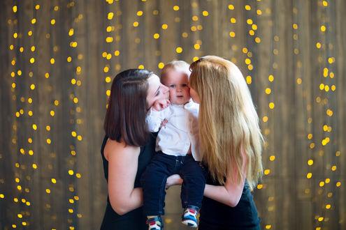 Фото Две девушки, держа малыша на руках, целуют его в обе щечки, фотограф Виктория Старцева