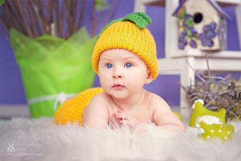 Фото Милый малыш в желтой шапочке и штанишках лежит на постели. Фотограф Марина Яблоновская