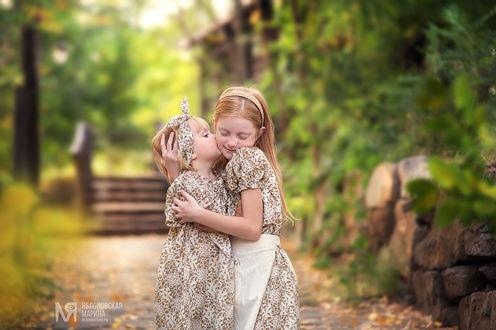 Фото Маленькая девочка целует и обнимает другую девочку. Фотограф Марина Яблоновская