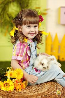 Фото Улыбающаяся девочка с цветами держит кролика на коленях. Фотограф Марина Яблоновская