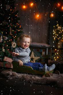 Фото Смеющийся кудрявый мальчик сидит в старых деревянных салазках на праздничном новогоднем фоне. Фотограф Лилия Ульянова