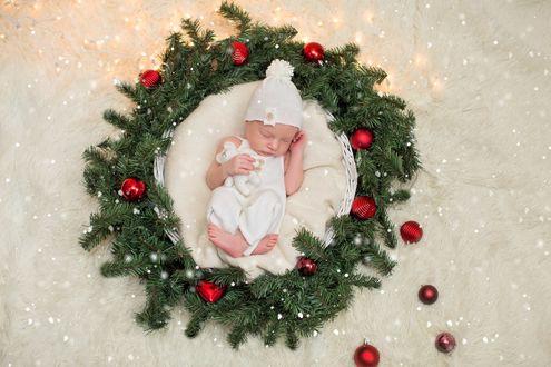 Фото Новорожденный малыш спит в корзинке, украшенной веточками ели и новогодними игрушками. Фотограф Лилия Ульянова