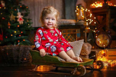 Фото Маленькая светловолосая девочка сидит в старых деревянных салазках на фоне праздничного новогоднего убранства. Фотограф Лилия Ульянова