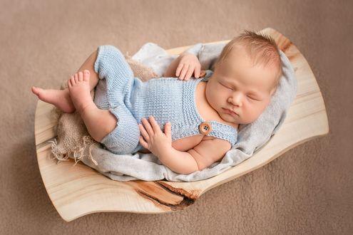 Фото Милый малыш в голубом вязанном комбинезоне сладко спит в деревянной люльке - качалке. Фотограф Лилия Ульянова
