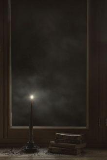Фото У окна на подоконнике стоит свеча и лежат книги