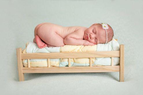 Фото Голенькая новорожденная малышка с украшением на голове сладко спит в кроватке. Фотограф Лилия Ульянова