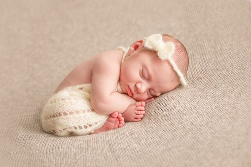 Фото Милая новорожденная девочка с вязанным бантиком на голове сладко спит. Фотограф Лилия Ульянова