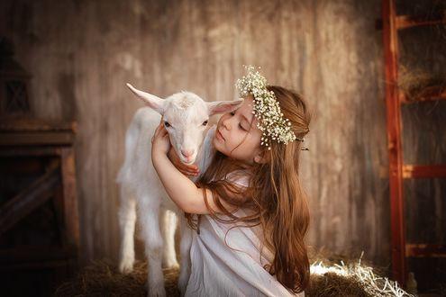 Фото Девочка в белом платье с венком из цветов на голове обняла козочку. Фотограф Лилия Ульянова