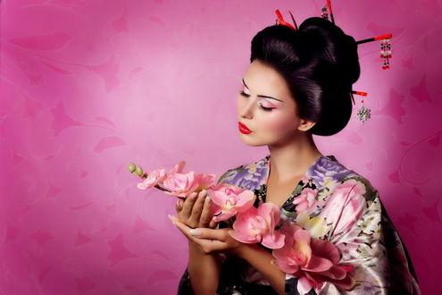 Фото Девушка японка с веточкой цветов в руках на розовом фоне