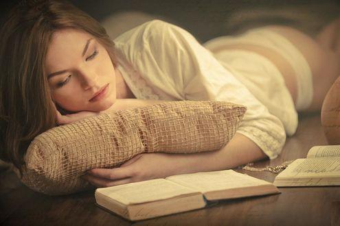 Фото Девушка лежит на полу с подушкой и читает книгу