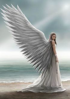 Фото Девушка с крыльями держит в руке ключ на побережье