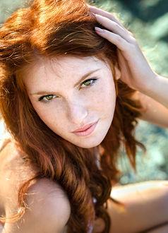 Фото Девушка с рыжими волосами и с веснушками рукой поправляет прическу. Фотограф Таня Маркова
