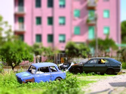 Фото На улице стоят два автомобиля, розовый дом на заднем плане