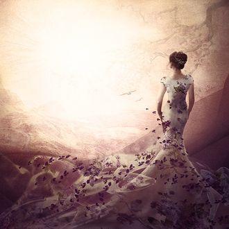 Фото Девушка в длинном платье с цветочным рисунком, с лепестками цветов на нем, стоит к нам спиной смотря вдаль