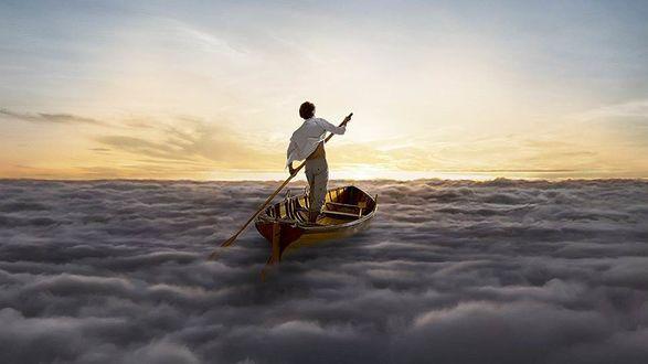 Фото Парень в лодке с веслом в руках на облаках на фоне неба