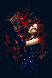 Фото Рыжеволосая девушка в синем платье и в синих перчатках держит в руках кораблик на фоне листьев. Фотограф Руслан Болгов