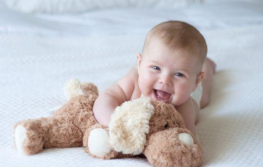 Фото Маленький малыш играет на полу с игрушкой