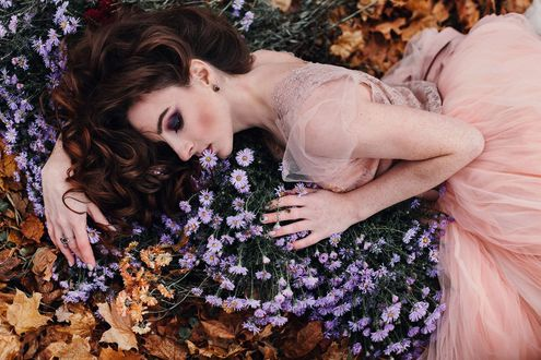 Фото Девушка в кремовом платье лежит на осенней листве с цветами. Фотограф Александр Джеймесон