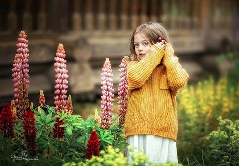 Фото Девочка стоит рядом с цветами и держит в руке цветочек, фотограф Недялкова Ирина