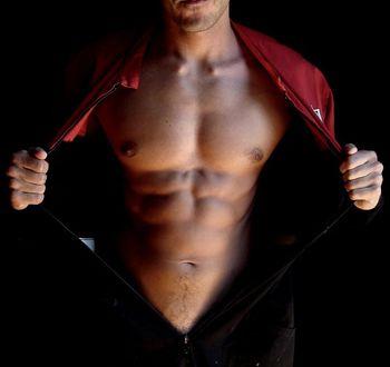 Фото Мужчина с идеальным телом расстегнул одежду и улыбается