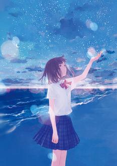 Фото Девушка в форме стоит у моря, подняв руку вверх