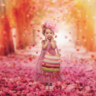 Фото Девочка с большим цветком на волосах, в розовом платье, с сумочкой стоит в цветах на фоне природы и летающих лепестков